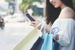 Woman shopping in shopping mall and use mobile phone shopping and find promotion. Business shopping situation idea concept.